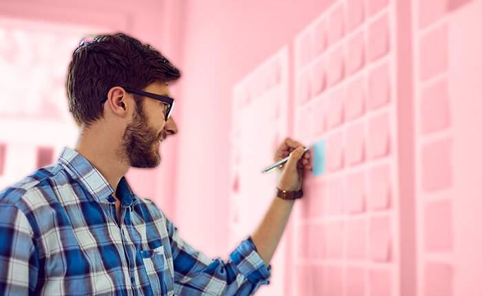 Etapas do planejamento estratégico - homem escrevendo em post-it no quadro